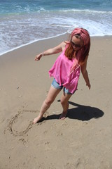 Beautiful rehead young woman drawing heart in the sand