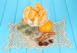 Tasty mandarine's slices in glass bowl on blue background