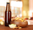 Crackers  and glass bottle of beverage, on bright background