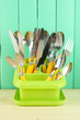 Knives, spoons, forks in plastic container for drying,