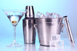 Metal ice bucket and shaker and cocktail on blue background