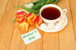Composition of tulips and cup with some drink,