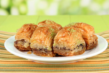 Sweet baklava on plate on table on bright background
