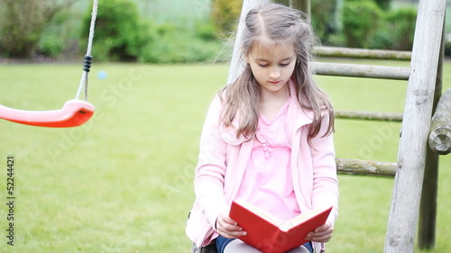 Little girl reading a book in summer
