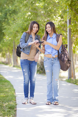 Young Adult Mixed Race Twin Sisters Sharing Cell Phone Experienc