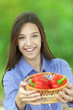 smiling teenage girl with basket of red peppers