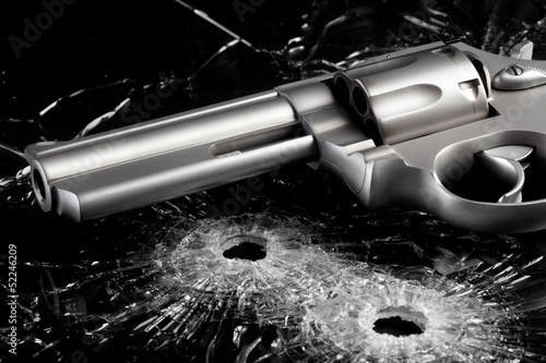 Gun with bullet holes in glass