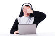 Nun working on laptop - religious concept