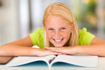 happy teen girl lying on book