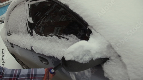Car in snow, woman cleans snow from car