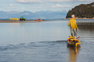 man pulling empty kayak across shallow water