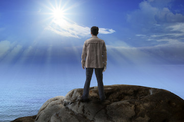 young man standing on rock mountain and looking to the sun