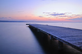 wooden pier with calm sea at sunset