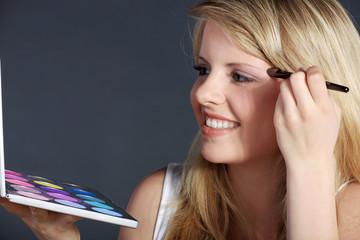Junge hübsche Frau schminkt sich mit Farbpalette