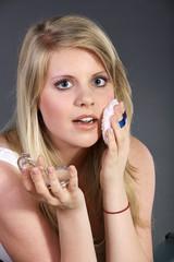 Junge hübsche Frau pudert sich im Gesicht ab