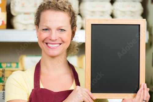 verkäuferin mit hinweistafel
