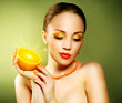 Girl with beautiful make-up holding orange fruit