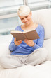 Smiling woman relaxing while reading a book on the sofa