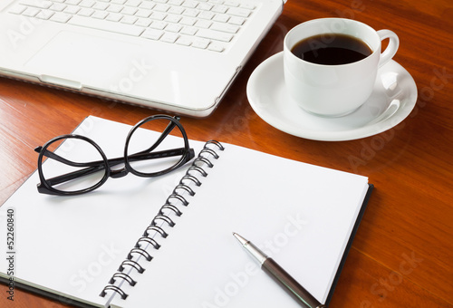 Laptop with cup of coffee and notepad on wooden background