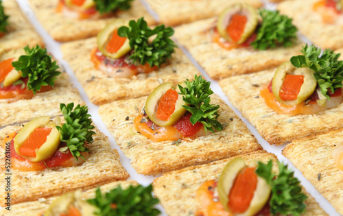 Baked wheat crackers topped with cheese, olives, and parsley