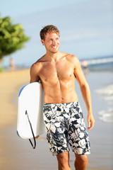 Man on beach holding body surfing bodyboard