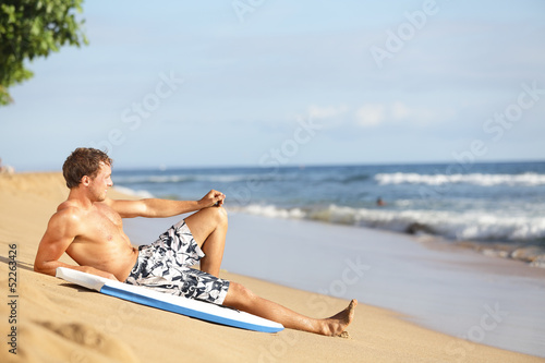 Beach man relaxing after surfing