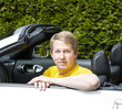 Mature man with arms on top of convertible car door