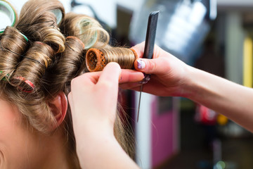 Woman at the hairdresser curling hair