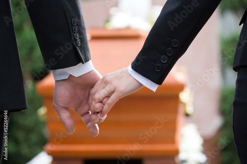 People at funeral consoling each other - 52264646