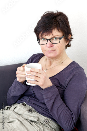 Woman with cup looking pensive