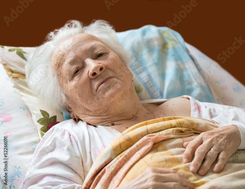 Old woman lying at bed