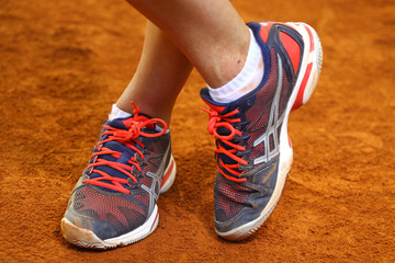 Tennis player legs on the clay court