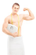 Handsome muscular man in towel holding a weight scale
