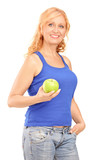 Middle aged woman holding a green apple and looking at camera