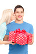 Young woman kissing a man with a present box