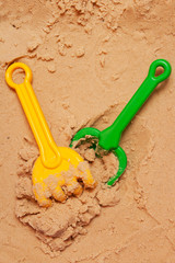 a beach shovel and a beach rake on the sand