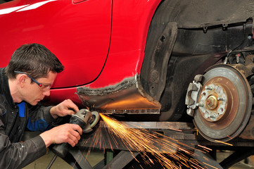 Man grinding welded car body.