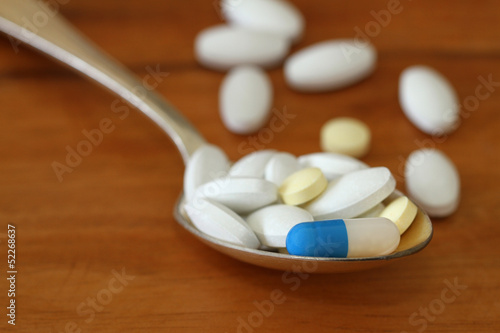 Spoon full of pills on wooden background, close up