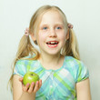 Laughing little girl with green apple