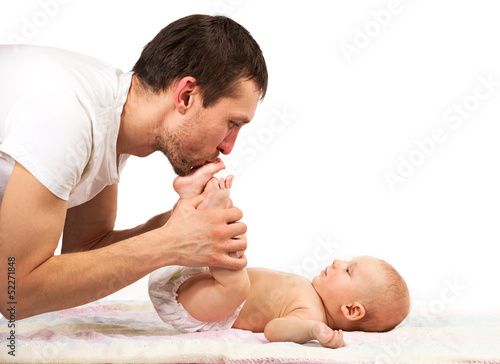 Young Caucasian father kissing feet of his baby son