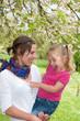 Junge Mutter mit ihrer Tochter auf dem Arm fröhlich lachend