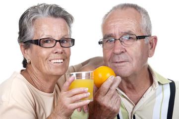 Vieux couple tenant dans la main un verre de jus d'orange et une