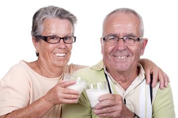 Couple âgé heureux en train de boire un verre de lait.