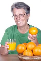 Dame âgée souriante avec un verre de jus d'orange