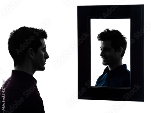 man serious in front of his mirror silhouette