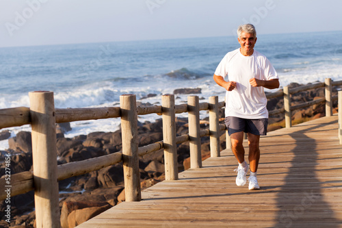 fit senior man running at the beach