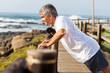 fit senior man exercising at the beach - 52275450