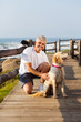 active senior man and his dog at the beach