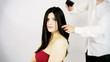 Hairdresser brushing long hair of beautiful woman