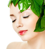 beautiful woman's face, surrounded by green leaves